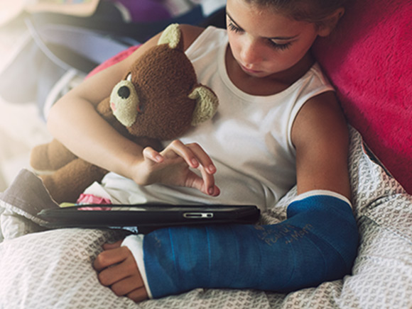 Little boy using a tablet with arm in a cast and teddy bear